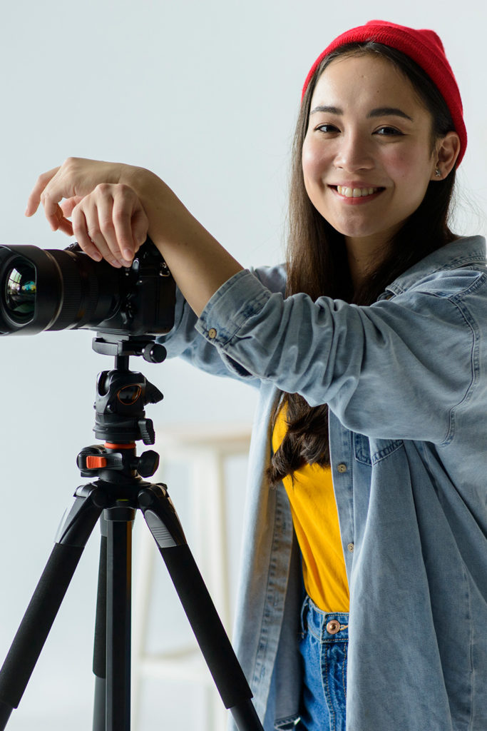 young woman smiling and resting on camera