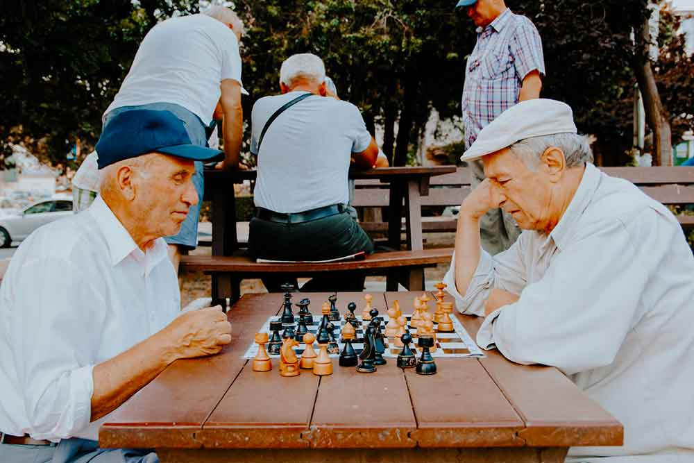 two older men playing chess in the park